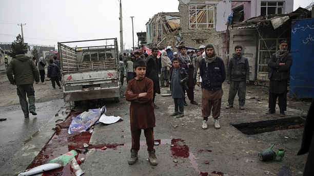 Residents walk through the site of a suicide attack in Kabul, Afghanistan, Friday, March 2, 2018. A large explosion in the eastern part of the Afghan capital on Friday morning killed at least one and wounding others officials said. (AP Photo/Massoud Hossaini)
