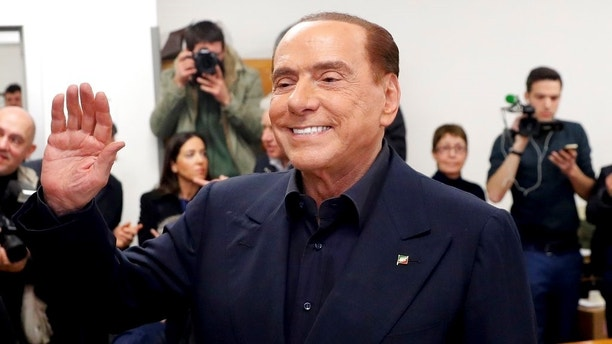 Italian former premier and leader of Forza Italia (Go Italy) party Silvio Berlusconi waves at a polling station in Milan, Italy, Sunday, March 4, 2018. More than 46 million Italians were voting Sunday in a general election that is being closely watched to determine if Italy would succumb to the populist, anti-establishment and far-right sentiment that has swept through much of Europe in recent years. (AP Photo/Antonio Calanni)