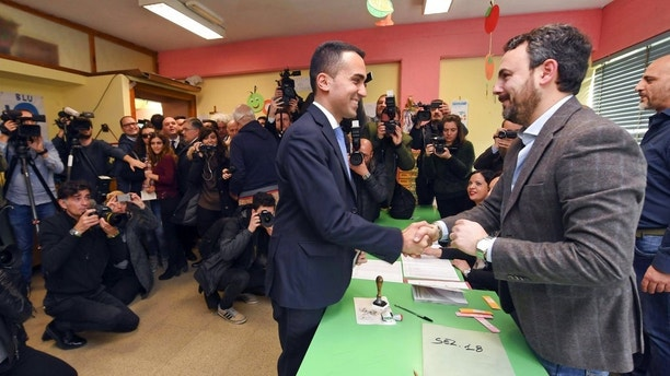 Five-Star movement's candidate premier Luigi Di Maio shakes hands with a polling clerk, right, as he votes in Pomigliano d'Arco, near Naples, Italy, Sunday, March 4, 2018.  More than 46 million Italians were voting Sunday in a general election that is being closely watched to determine if Italy would succumb to the populist, anti-establishment and far-right sentiment that has swept through much of Europe in recent years. (Ciro Fusco/ANSA via AP)