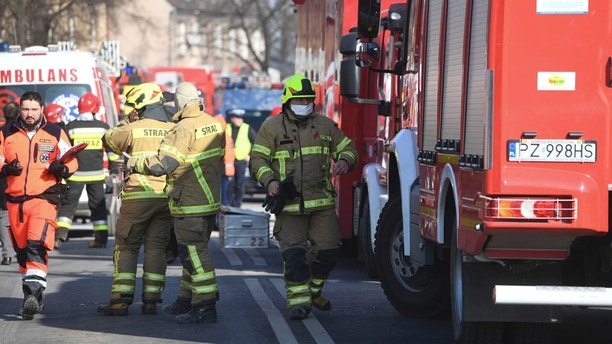 Firefighters and rescuers  work at the scene of a building collapse in Poznan, Poland, Sunday, March 4, 2018. An apartment block collapsed Sunday in Poland's western city of Poznan, killing several people and injuring more than 20 others, officials said as teams of firefighters and rescuers with dogs combed the rubble in search of more victims. (AP Photo/Str)