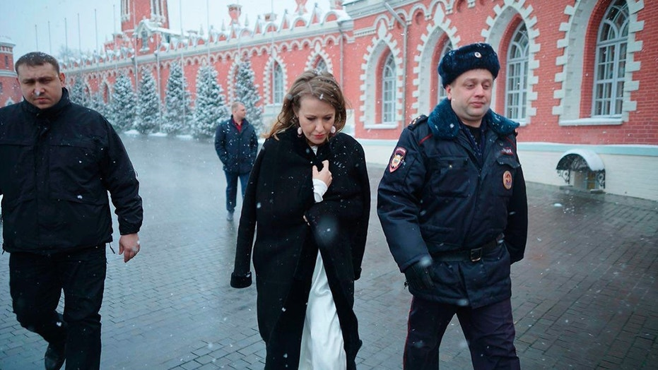 In this handout photo released by Russian presidential candidate Ksenia Sobchak's press service, Ksenia Sobchak, center, walks with a police officer after she was doused with water and knocked to the ground in an assault in Moscow, Russia, Sunday, March 4, 2018.