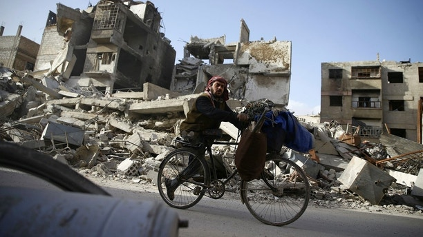 A handicapped man rides a bicycle past damaged buildings in the besieged town of Douma in eastern Ghouta in Damascus, Syria, March 1, 2018. REUTERS/Bassam Khabieh - RC19231603F0