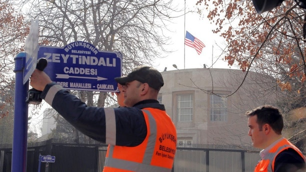 """FILE - In this Feb. 19, 2018 file photo, an Ankara municipality worker fixes the new street sign, """"Olive Branch Street"""" in Turkish, near the U.S. embassy, at rear, in Ankara, Turkey. The U.S. Embassy in Turkey will be closed on Monday due to an unspecified security threat. (AP Photo/Burhan Ozbilici, File)"""