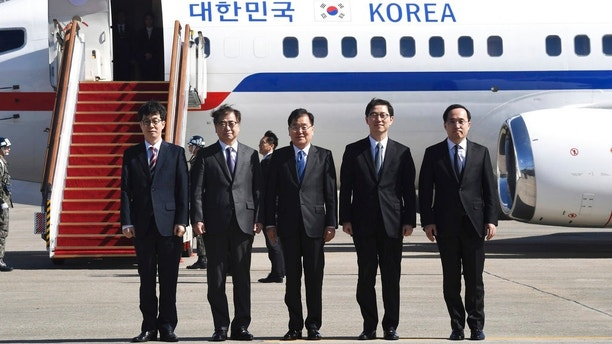 South Korea's national security director Chung Eui-yong, center, National Intelligence Service Chief Suh Hoon, second left,  and other delegators pose before boarding an aircraft as they leave for Pyongyang at a military airport in Seongnam, south of Seoul, Monday, March 5, 2018. A group of high-level South Korean officials has left for North Korea for talks on North Korea's nuclear program and ways to help resume talks between Pyongyang and Washington. (Jung Yeon-je/Pool Photo via AP)