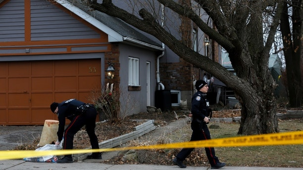 Police officers guard the grounds of a house they had searched, after a landscaper was accused of murdering five people and putting their dead bodies in large planters on his clients' properties, in Toronto, Ontario, Canada January 29, 2018. REUTERS/Chris Donovan - RC171835DE40