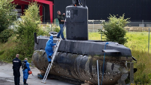 FILE - This is a Sunday, Aug. 13, 2017, file photo of police technicians board Peter Madsen's submarine UC3 Nautilus on a pier in Copenhagen harbour, Denmark. Peter Madsen stands trial at Copenhagen's City Court on Thursday March 8, 2018, for the killing of Kim Wall, 30, in his submarine off the usually quiet northern European country. (Jacob Ehrbahn/Ritzau Foto, File via AP)