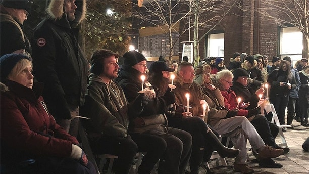 In this Feb. 13, 2018 photo, people hold a candlelight vigil to remember the victims of alleged serial killer Bruce McArthur in Toronto, Canada. Some of the known and suspected victims of the alleged serial killer fit a pattern: people on the margins of Canadian society whose disappearance attracted little attention, until LGBQT activist and former bartender with many friends, Andrew Kinsman, vanished. (AP Photo/Rob Gillies)