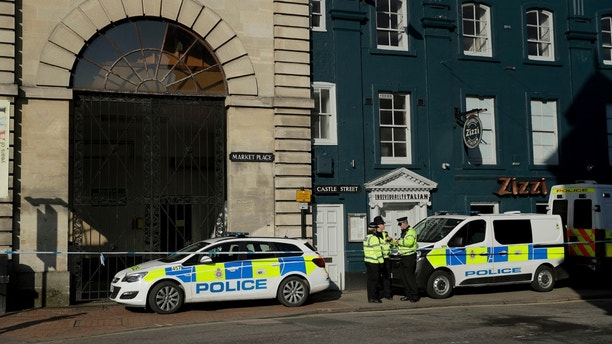 """Police officers stand outside a Zizzi restaurant in Salisbury, England, Wednesday, March 7, 2018, near to where former Russian double agent Sergei Skripal was found critically ill. Britain's counterterrorism police took over an investigation Tuesday into the mysterious collapse of the former spy and his daughter, now fighting for their lives. The government pledged a """"robust"""" response if suspicions of Russian state involvement are proven. Sergei Skripal and his daughter are in a critical condition after collapsing in the English city of Salisbury on Sunday. (AP Photo/Matt Dunham)"""