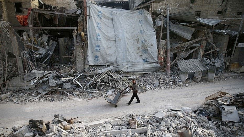 A man pushes a cart past damaged buildings in Syria this week.