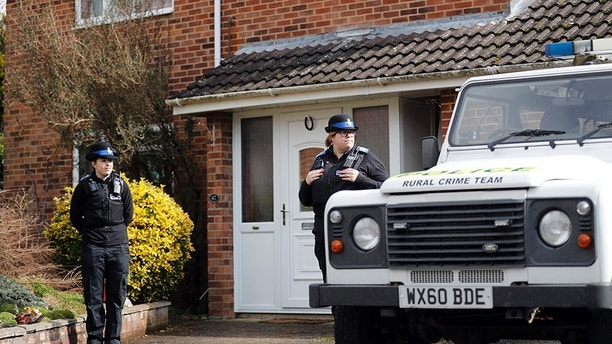 """Police officers stand outside the house of former Russian double agent Sergei Skripal who was found critically ill Sunday following exposure to an """"unknown substance"""" in Salisbury, England, Tuesday, March 6, 2018. Skripal, and an unidentified woman companion are being treated in hospital, after they were found unconscious on a  bench in the town. (AP Photo/Frank Augstein)"""
