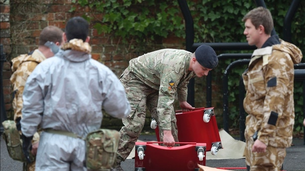 Military personnel outside Bourne Hill police station in Salisbury, England, as police and members of the armed forces probe the suspected nerve agent attack on Russian double agent spy Sergei Skripal, Sunday March 11, 2018. British government security ministers held an emergency meeting Saturday to discuss the poisoning of former spy Skripal and his daughter Yulia, as police backed by soldiers continued to search the English town where he was attacked with a nerve agent. (Andrew Matthews/PA via AP)
