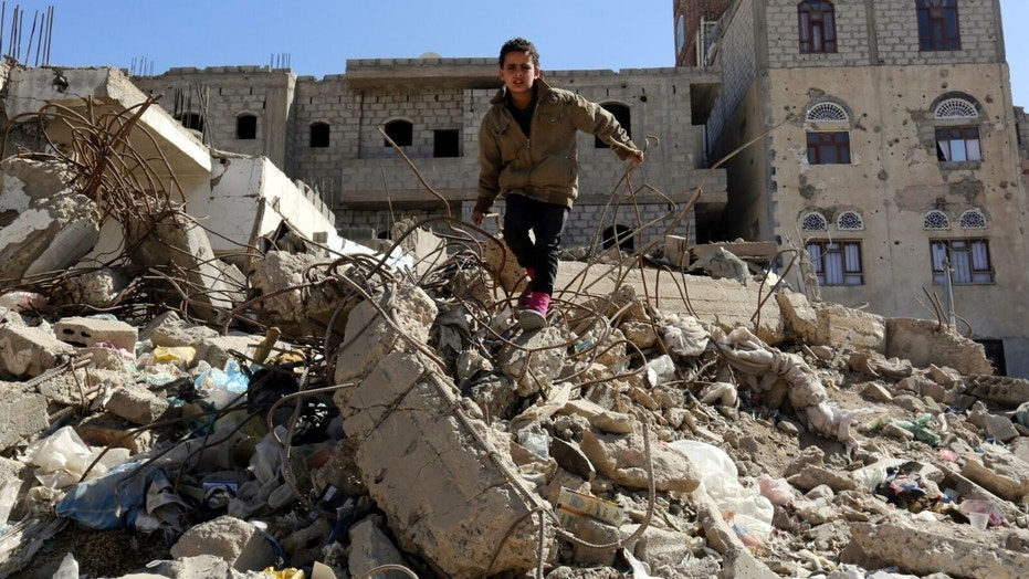 Sana'a. A child stands in the middle of destroyed buildings in his neighborhood.