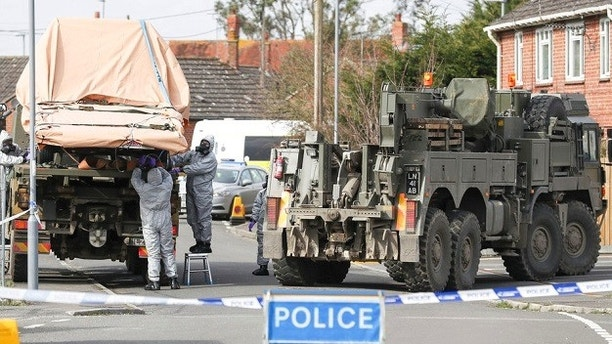 Soldiers wearing protective clothing  lift a tow truck in Hyde Road, Gillingham, Dorset, England as the investigation into the suspected nerve agent attack on Russian double agent Sergei Skripal continues Wednesday March 14, 2018.  The army cordoned off a road in Dorset on Wednesday as the investigated the attack on Sergei Skripal and his daughter Yulia. Authorities have cordoned off several sites in and near Salisbury, 90 miles (145 kilometers) southwest of London as part of their probe.  (Andrew Matthews/PA via AP)