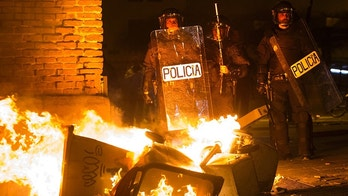 Spanish National Police officers take positions next to a burning barricade during clashes with demonstrators in Lavapies, a neighbourhood of Madrid, Spain, Thursday, March 15, 2018. Street clashes erupted Thursday night in central Madrid over the death of a 35-year-old African vendor who witnesses said died trying to escape from police cracking down on illegal street sales. (AP Photo/Alejandro Martinez Velez)