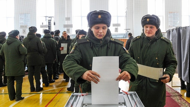 Russian soldiers cast their ballots in the presidential election at the polling station in Rostov-ojn-Don, Russia, Sunday, March 18, 2018. Russia's presidential election was tainted Sunday by unprecedented pressure on voters to turn out and incidents of suspected ballot box stuffing, a barely democratic exercise that will grant Vladimir Putin another six years of power. (AP Photo)