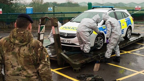 In this image dated Friday March 9, 2018, and issued Saturday March 10, 2018, by Britain's Ministry of Defence, showing troops in protective gear as they work to remove a contaminated police car from the Accident and Emergency entrance at the District Hospital in Salisbury, England. Counter-terrorism police asked for military assistance to remove vehicles and objects from the scene in the city, much of which has been cordoned off over contamination fears of the nerve agent poisoning of former spy Sergei Skripal and his daughter. (Pete Brown/MoD via AP)