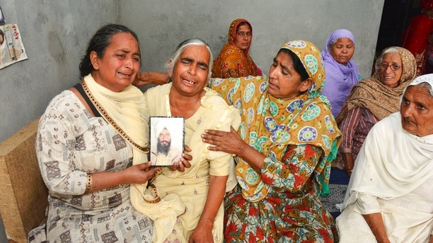 Relatives mourn holding a portrait of Gurcharan Singh, one of the 38 Indian workers whose bodies were found buried northwest of Mosul, in Jalal Usma village in the northern Indian state of Punjab, Tuesday, March 20, 2018. Iraqi authorities have found the bodies of 38 Indian workers abducted when Islamic State militants overran the northern city of Mosul more than three years ago, officials said Tuesday. (AP Photo/Prabhjot Gill)