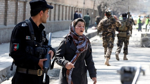 An Afghan woman seeks for her relative at the site of a suicide in Kabul, Afghanistan March 21, 2018. REUTERS/Omar Sobhani - RC15635D9830