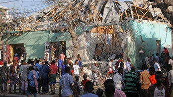 Somalis stand outside a destroyed building after a car bomb in Mogadishu, Somalia Thursday, March 22, 2018. Somali officials say at least 14 people have been killed and 10 others are wounded in a car bomb blast near a hotel in the capital, Mogadishu. (AP Photo/Farah Abdi Warsameh)