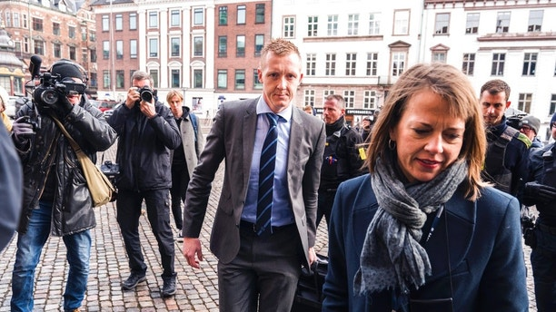 Prosecutor Jakob Buch-Jepsen, centre,  arrives for the second hearing at the courthouse where the trial of Danish inventor Peter Madsen, charged with murdering and dismembering Swedish journalist Kim Wall aboard his homemade submarine continues, in Copenhagen, Wednesday, March 21, 2018. The murder trial of the Danish inventor accused of torturing and killing a Swedish journalist during a private submarine trip has resumed after a two-week hiatus, with testimony from the defendant. (Martin Sylvest/Ritzau Scanpix via AP)