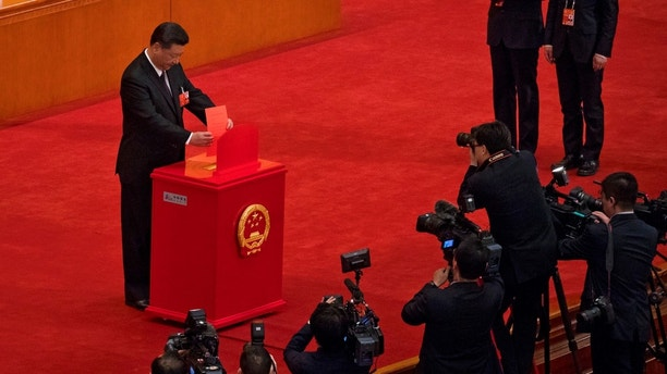 In this Saturday, March 17, 2018, photo, Chinese journalists film Chinese President Xi Jinping casts his ballot during a plenary session of China's National People's Congress at the Great Hall of the People in Beijing. The Chinese Communist Party's move to exert direct control over state broadcasters and regulators of everything from movies and TV to books and radio programs shows the party's drive to use the media for ideological efforts at home and to improve its image overseas, analysts say. The move is part of a push by Xi to tighten party supervision over much of Chinese public life as he renews his uncontested rule free of constitutional limits on his terms in office. (AP Photo/Andy Wong)