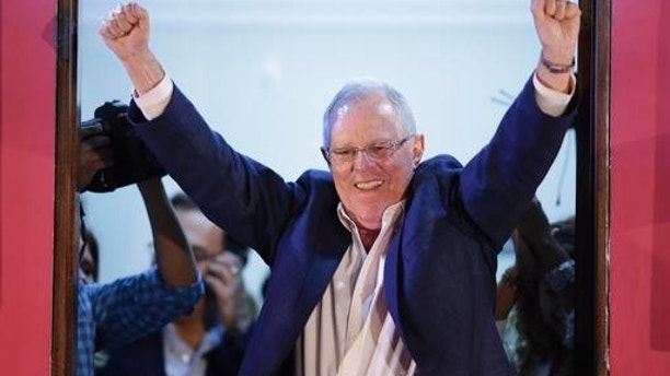 Presidential candidate Pedro Pablo Kuczynski celebrates from the balcony of his headquarter in Lima, Peru, Sunday, June 5, 2016. Early exit polls show presidential candidate Pedro Pablo Kuczynski with a slight lead over his rival Keiko Fujimori in Peru's runoff presidential election.(AP Photo/Martin Mejia)