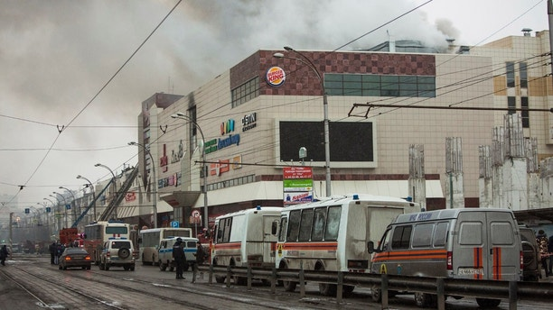 Smoke rises above a multi-story shopping center in the Siberian city of Kemerovo, about 3,000 kilometers (1,900 miles) east of Moscow, Russia, on Sunday, March 25, 2018. At least three children and a woman have died in a fire that broke out in a multi-story shopping center in the Siberian city of Kemerovo. (AP Photo/Sergei Gavrilenko)