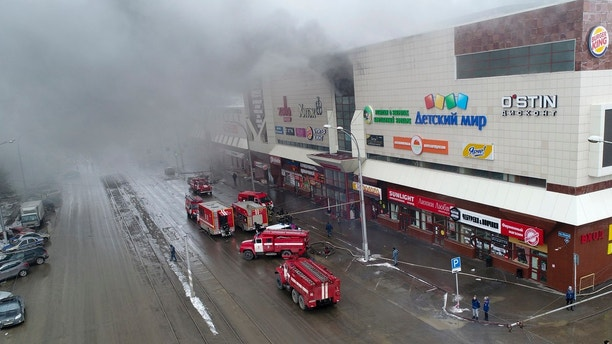 In this Russian Emergency Situations Ministry photo on Sunday, March 25, 2018, smoke rises above a multi-story shopping center in the Siberian city of Kemerovo, about 3,000 kilometers (1,900 miles) east of Moscow, Russia. At least three children and a woman have died in a fire that broke out in a multi-story shopping center in the Siberian city of Kemerovo. (Russian Ministry for Emergency Situations photo via AP)