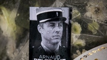 """A photo of Lieutenant Colonel Arnaud Beltrame placed on a bunch of flowers at the main gate of the Police headquarters in Carcassonne, France, Saturday, March 24, 2018, following an attack on a supermarket in Trebes in the south of the country on Friday. A French police officer who offered himself up to an Islamic extremist gunman in exchange for a hostage died of his injuries, raising the death toll in the attack to four, and the officer was honored Saturday as a national hero of """"exceptional courage and selflessness."""" (AP Photo/Emilio Morenatti)"""