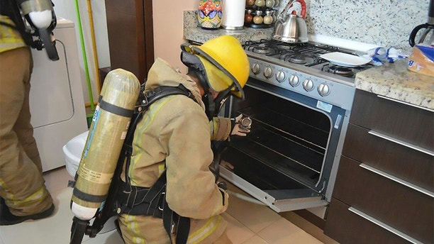 Photo provided by the Fiscal Office of Quintana Roo, a fireman examines a gas stove in the rented condominium where an Iowa couple and their two children died in Tulum, Mexico. Mexican authorities said on Saturday, March 24, 2018 that the autopsies of his two sons died from inhaling toxic gas in the rented condominium on the Caribbean coast of Mexico, but there were no signs of foul play or suicide. (Prosecutor's Office of Quintana Roo via AP)