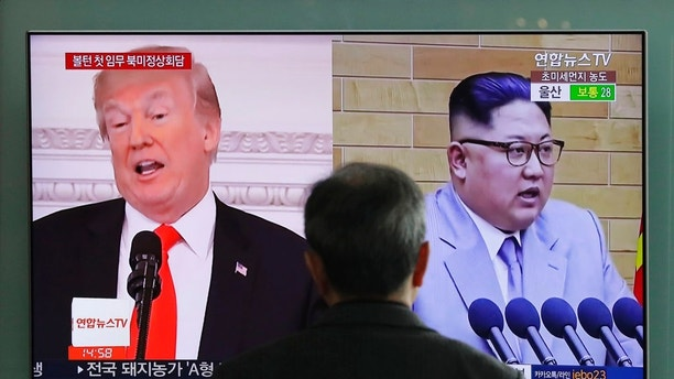 A man watches a TV screen showing file images of U.S. President Donald Trump left and North Korean leader Kim Jong Un right during a news program at the Seoul Railway Station in Seoul South Korea Tuesday