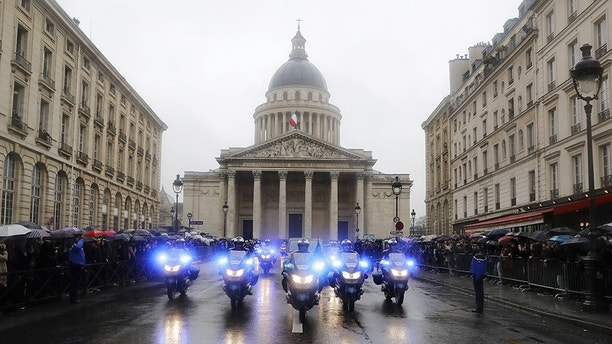 Police officers escort for the coffin of late Lieutenant Colonel Arnaud Beltrame before a funeral procession outside the Pantheon in Paris,Wednesday, March 28, 2018. The slain hero of last week's extremist attack in southern France will be posthumously awarded the Legion of Honor by French President Emmanuel Macron Wednesday during a solemn day-long national homage to him.(Etienne Laurent, Pool via AP)