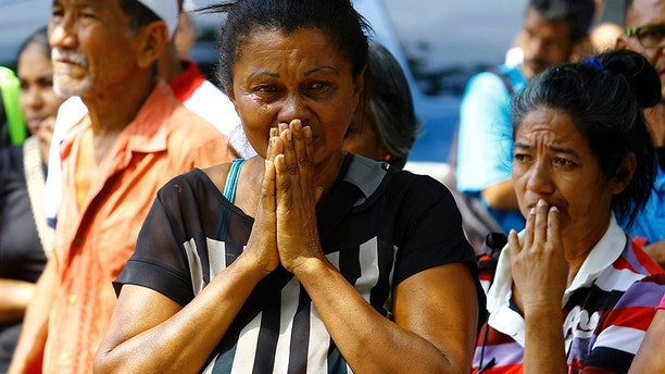 Relatives wait to hear news about the fate of detained prisoners at a police station where a riot broke out, in Valencia, Venezuela, Wednesday, March 28, 2018. In a state police station housing more than one hundred prisoners, a riot culminated in a fire, requiring authorities to open a hole in a wall to rescue the inmates. (AP Photo/Juan Carlos Hernandez)