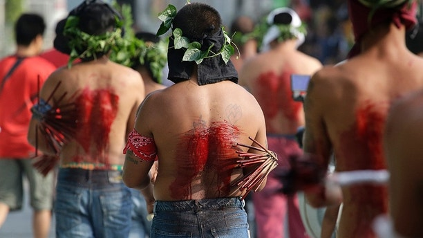 Filipino penitents line up as they flagellate during Good Friday rituals to atone for sins in San Fernando, Pampanga province, northern Philippines, Friday, March 30, 2018. The ritual is frowned upon by church leaders in this predominantly Roman Catholic country. (AP Photo/Aaron Favila)