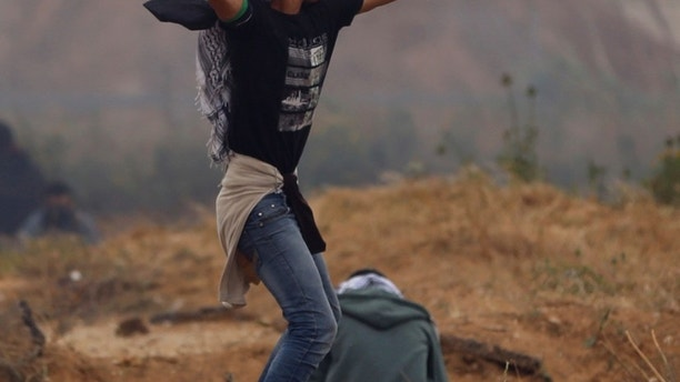 A Palestinian protester hurls stones toward Israeli soldiers during a demonstration near the Gaza Strip border with Israel, in eastern Gaza City, Friday, March 30, 2018. (AP Photo/Khalil Hamra)