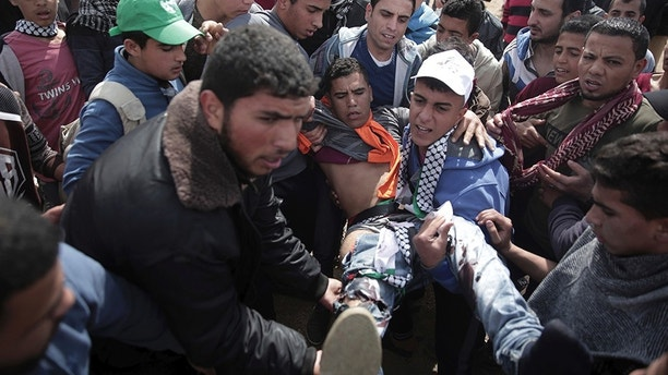 Palestinian protesters carry a wounded man was shot by Israeli troops during a demonstration near the Gaza Strip border with Israel, in eastern Gaza City, Friday, March 30, 2018. (AP Photo/ Khalil Hamra)
