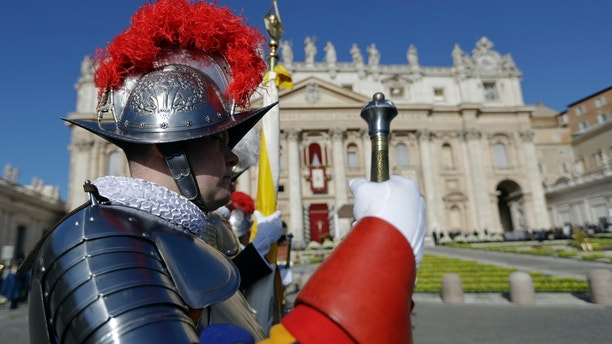 Vatican Swiss Guards stand at attention in front of St. Peter's Basilica at the Vatican prior to the arrival of Pope Francis to celebrate an Easter mass, Sunday, April 1, 2018. (AP Photo/Andrew Medichini)