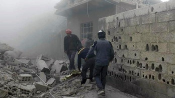 This photo provided by the Syrian Civil Defense White Helmets, which has been authenticated based on its contents and other AP reporting, shows members of the Syrian Civil Defense group and civilians gathering to help survivors from a street attacked by airstrikes and shelling by Syrian government forces in Ghouta, a suburb of Damascus, Syria, Friday, March. 2, 2018. The Russia-ordered pause came after a U.N. Security Council resolution calling for a nationwide 30-day cease-fire failed to take hold. While the relentless bombing has somewhat subsided in eastern Ghouta, home to around 400,000 civilians, the Syrian government's push to squeeze the insurgents out of the region continued. (Syrian Civil Defense White Helmets via AP)
