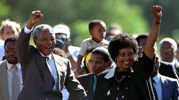 Nelson Mandela, accompanied by his wife Winnie, walks out of the Victor Verster prison near Cape Town after spending 27 years in apartheid jails in this February 11, 1990 file photo. REUTERS/Ulli Michel/Files  (SOUTH AFRICA - Tags: CIVIL UNREST POLITICS TPX IMAGES OF THE DAY)
