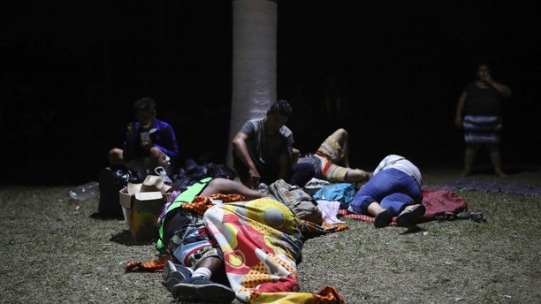 Central American migrants, who are participating in the annual Migrant Stations of the Cross caravan, go to sleep on the grass during the group's stop at a sports center in Matias Romero, Oaxaca state, Mexico, late Monday, April 2, 2018. The annual caravans have been held in southern Mexico for years as an Easter-season protest against the kidnappings, extortion, beatings and killings suffered by many Central American migrants as they cross Mexico. (AP Photo/Felix Marquez)