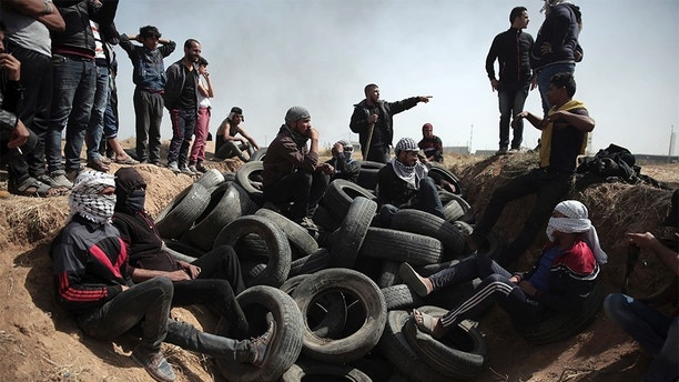 Palestinian protesters sit over tens of tires collected to be burned during a protest at the Gaza Strip's border with Israel, Friday, April 6, 2018. (AP Photo/ Khalil Hamra)