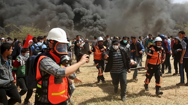 Palestinian protesters and civil defense evacuate a wounded youth during clashes with Israeli troops along Gaza's border with Israel, Friday, April 6, 2018. (AP Photo/Adel Hana)