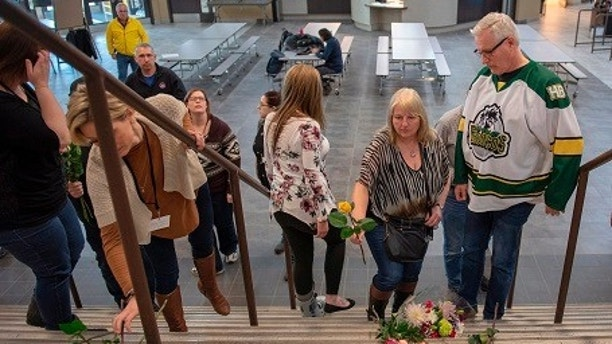 Humboldt mayor Rob Muench, in the Broncos team jersey, along with other mourners lay down flower on the stairs that enter to Elgar Petersen Arena, home of the Humboldt Broncos, in Humboldt, Saskatchewan, Canada on Saturday, April 7, 2018.  Canadian police said early Saturday that several people were killed and others injured after a truck collided with a bus carrying the junior hockey team to a playoff game in Western Canada. Police say there were 28 people, including the driver, on board the bus of the Humboldt Broncos team when the crash occurred around 5 p.m. Friday on Highway 35 in Saskatchewan.   (Liam Richards/The Canadian Press via AP)