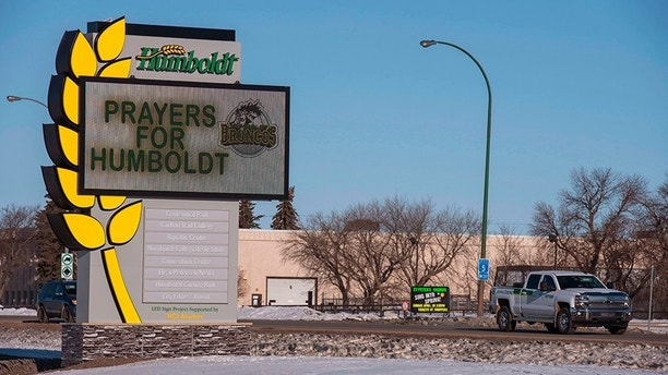 A truck drives by the welcome sign honoring the members of the Humboldt Broncos hockey team in Humboldt, Saskatchewan, Canada,  Saturday, April 7, 2018. Canadian police said early Saturday that several people were killed and others injured after a truck collided with a bus carrying the junior hockey team to a playoff game in Western Canada. Police say there were 28 people, including the driver, on board the bus of the Humboldt Broncos team when the crash occurred around 5 p.m. Friday on Highway 35 in Saskatchewan.   (Liam Richards/The Canadian Press via AP)