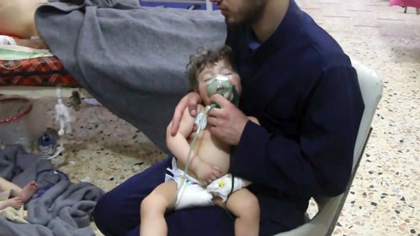 This image made from video released by the Syrian Civil Defense White Helmets, which has been authenticated based on its contents and other AP reporting, shows a medical worker giving toddlers oxygen through respirators following an alleged poison gas attack in the opposition-held town of Douma, in eastern Ghouta, near Damascus, Syria, Sunday, April 8, 2018. Syrian opposition activists and rescuers said Sunday that a poison gas attack on a rebel-held town near the capital. The Syrian government denied the allegations, which could not be independently verified. (Syrian Civil Defense White Helmets via AP)