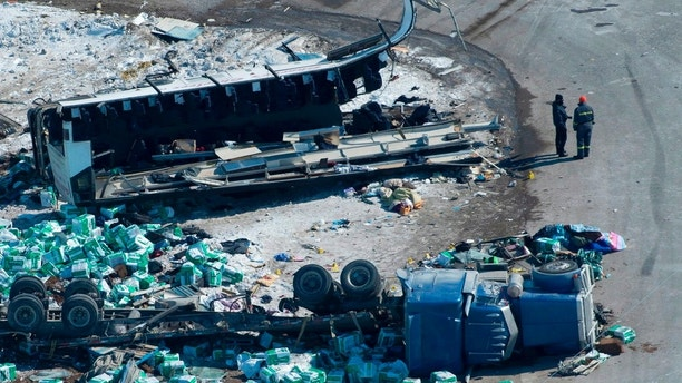 The wreckage of a fatal crash outside of Tisdale, Sask., is seen Saturday, April, 7, 2018. A bus carrying the Humboldt Broncos hockey team crashed into a truck en route to Nipawin for a game Friday night killing 14 and sending over a dozen more to the hospital. (Jonathan Hayward/The Canadian Press via AP)