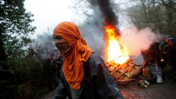 A protestor walks past burning debris as French gendarmes continue an evacuation operation in the zoned ZAD (Deferred Development Zone) in Notre-Dame-des-Landes, near Nantes, France, April 9, 2018. REUTERS/Stephane Mahe - RC1AFCEAA030