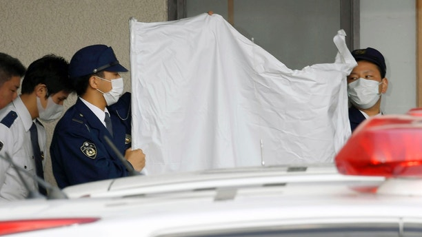 Police officers hide the face of arrested Japanese Yoshitane Yamasaki with a sheet while escorting him to a police vehicle to leave for Prosecutor's Office for further investigation, in Sanda City, western Japan, Monday, April 9, 2018. Japanese police arrested the 73-year-old man who reportedly kept his disabled son in a small wooden cage for more than 20 years. (Yohei Nishimura/Kyodo News via AP)
