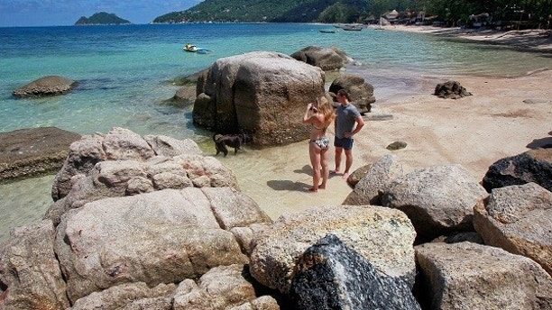 FILE PHOTO: Tourists take pictures on the island of Koh Tao September 19, 2014.  REUTERS/Chaiwat Subprasom/File Photo - RC139C59A690