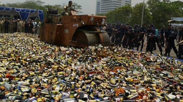 Indonesian government officials destroy alcoholic drinks that were raided from shops without alcohol permits in Jakarta November 9, 2004. Officials have amassed about 23,000 bottles of liquor and other alcoholic drinks in an effort to crack down on crime in Indonesia, home to the world's largest Muslim nation. REUTERS/Enny Nuraheni en/CN   BEST QUALITY AVAILABLE - GF2E4620ZAB01